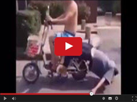 Koleś ciągnie głową za skuterem